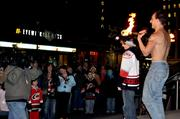 A fire-dancer brings a kid from the crowd to participate in a trick.