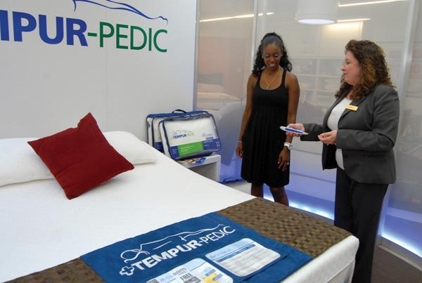 Sleepy's North Hills store manager Gayle Celentano, right, shows Cemone Moy a Tempur-pedic mattress.