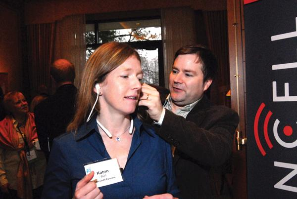 Steven LeBoeuf helps Katrin Burt of Intersouth Partners with a set of Valencell headphones.