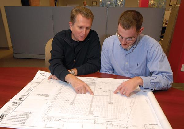 Strata Solar CEO Markus Wilhelm, left, goes over plans with Michael Cohen.