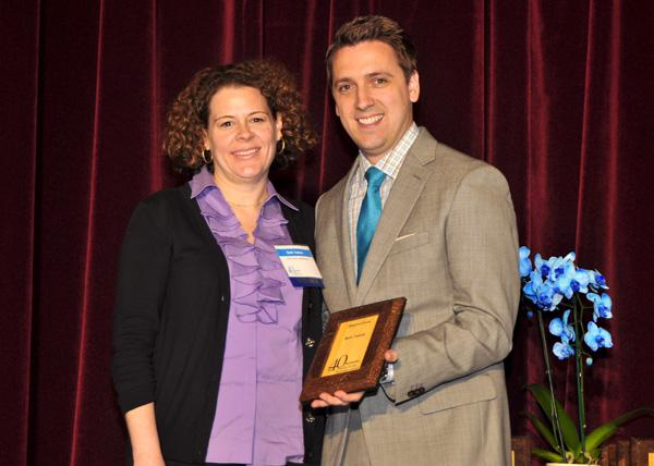 Beth Trahos accepts her award from TBJ Publisher Bryan Hamilton