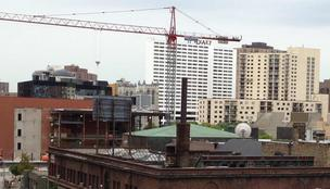 Tower cranes, like this one with a Mortenson sign above Orchestra Hall in Minneapolis, should become a more common site due to a recent jump in Twin Cities building contracts.