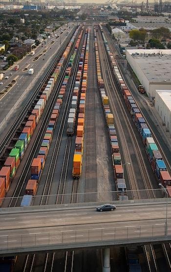 Freight trains sit in the Alameda Corridor as a car drives across an overpass in Los Angeles on Friday. The Alameda Corridor, a 20-mile-long rail cargo expressway linking the ports of Long Beach and Los Angeles, is a $2.4 billion project that consolidated three rail lines and includes bridges, underpasses and overpasses that separate freight trains from automobiles.