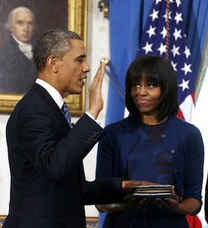 First Lady Michelle Obama holds the family Bible and watches as U.S. President Barack Obama is officially sworn-in in the Blue Room of the White House during the 57th Presidential Inauguration in Washington, D.C., U.S., on Sunday.