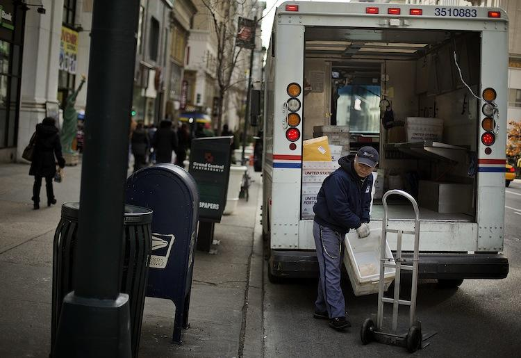 A U.S.PostalService(USPS) employee takes mail out of a truck for delivery in New York. The USPS is ready to cut Saturday mail after reporting a loss last year of$15.9billion.