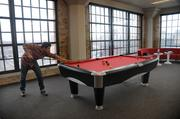 Paul Shively playing pool in the company's playroom.