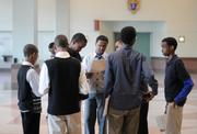 A group of boys look over the interview score sheets they received from the businesspeople with whom they interviewed.
