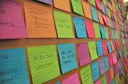Employees use a wall of Post-it Notes to list goals and achievements.