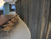 A chain curtain divides a lunch room from the lobby area. It can slide open to accommodate different group sizes.