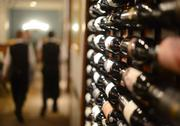 A wide selection of wine is displayed along a wall.