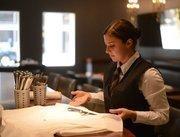 Marie Laudenbach rolls silverware into linen napkins