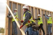 Crew leader Rollie Johnson (foreground with hammer) helps someCEOs raise a wall.