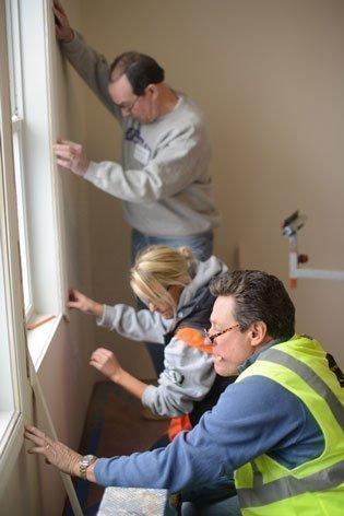 Warren Staley (top), formerCEO of Cargill Inc.; Phoebe Novitski, an AmeriCorp volunteer; and Tim Murnane,CEO of Opus, work on putting up window trim.