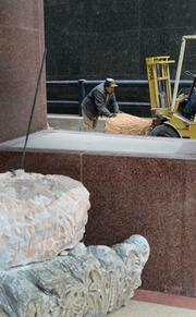 Maneuvering pieces of the sculpture into place.