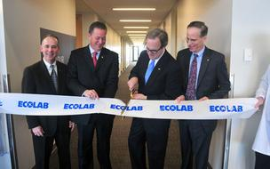 Ecolab CEO Doug Baker cuts the ribbon to open the new training center. With him are (left to right) Rick Johns, Mike Hickey and Larry Berger.