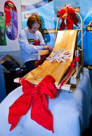 Rosie Sato wraps a vintage sled in 3M's National Gift Wrapping Contest.
