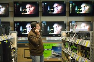 A customer talks on a mobile phone as he looks at electronics for sale at a Best Buy store in San Francisco.