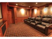 A theater room that includes a projector, theater-grade sound and video, and large, leather chairs.