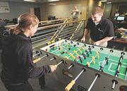 Fishbowl Solutions Inc. Marketing Associate Kim Negaard and Software Consultant Nathan Stocker play a game of foosball in the company's breakroom.