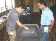 ILM Professional Services Inc. President Farhan Muhammad, right, and Developer John Smith, playing checkers on surface technology.