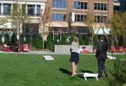 The main atrium at Target Plaza Commons is connected with a big glass garage door to the grassy backyard, where these employees are playing bean bag toss.