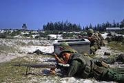 Battle of Hamo Village during the Tet Offensive. U.S. Marines and troops from the Army of the Republic of Vietnam defend a position against enemy attack. January 1968. (Courtesy National Archives and Records Administration)