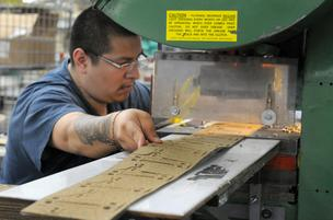 Juan Gonzalez, a press operator at Precision Gasket Co., uses a punch press to cut out gaskets. Sales are up 20 percent.