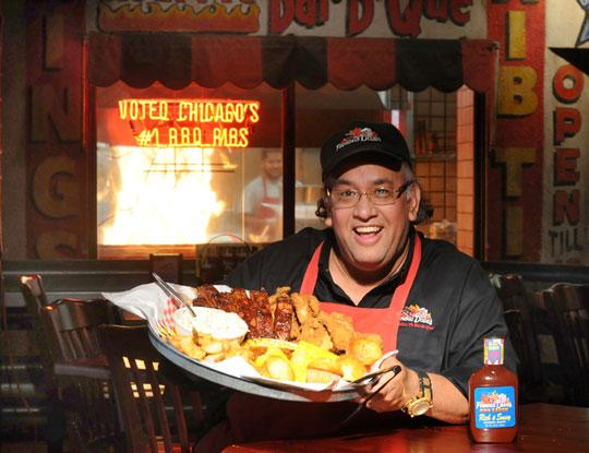 Nancy Kuehn | Minneapolis/St. Paul Business Journal  Dave Anderson, founder of Famous Dave's of America, with a plate of the company's award-winning ribs at the Famous Dave's in Calhoun Square, Minneapolis.