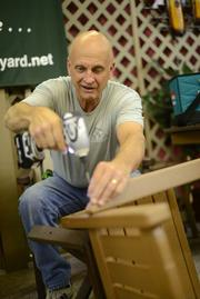 Roger Anderson, left, an owner of By the Yard Inc., sets up his firm's yard furniture at the State Fair this week.