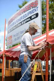 John Patoch, manager for Beisswenger, hanging signs before the fair opened this week.