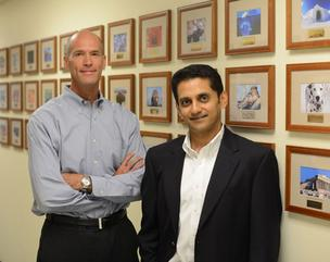"Surmodics CEO Gary Maharaj, right, and CFO Tim Arens. The pictures behind them represent customers (the company encodes its clients with names like ""dalmatian"" and ""pretzel."""
