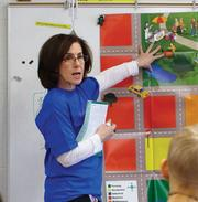 """Deluxe volunteer Terri Shapiro talks to students at a """"JA in a Day"""" event."""