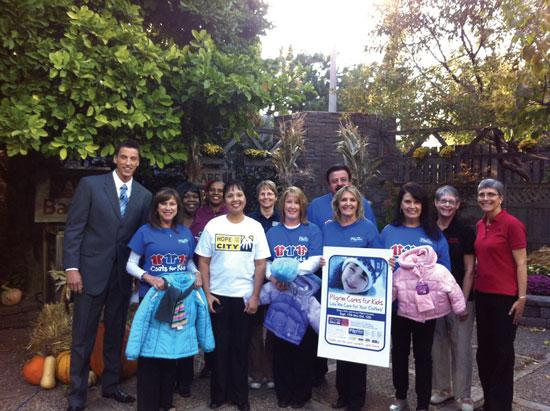 Meteorologist Jerrid Sebesta stands with organizers of Coats for Kids.