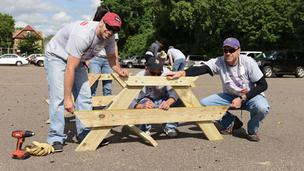 Toro volunteers put together a picnic table at the Toro/Vikings KaBOOM! Playground Build event at Sheridan Arts Magnet School.