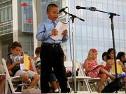 A student speaks at a Travelers Young Writers Reading event.