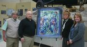 Three pieces of artwork honoring military personnel have found new homes  at the National Museum of the Marine Corps. From left, Azalea Charities Director Pete Robinson, Azalea Charities founder and chairman Frank Lasch, museum director Lin Ezell and museum curator Vickie Stuart-Hill.