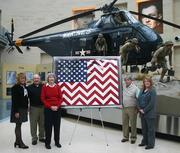 Three pieces of artwork honoring military personnel have found new homes at the National Museum of the Marine Corps. Presenting an original quilt to the museum are, from left, Museum Director Lin Ezell, Azalea Charities founder and chairman Frank Lasch, quilt creator Betty Harland, Azalea Charities Director Pete Robinson and museum curator Vickie Stuart-Hill.