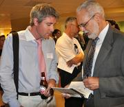 """Qorvis Communications celebrated the publication of """"Red Ink: Inside the  High Stakes Politics of the Federal Budget,"""" by David Wessel, economics  editor of The Wall Street Journal, during a reception Aug. 2 at its  D.C. offices. Robert Grant of the British Embassy, left, with Wessel."""