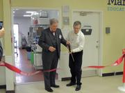 Edward Allera, left, co-managing shareholder of Buchanan Ingersoll & Rooney, and Michael Bartscherer, interim president of Martha's Table, cut the ribbon.