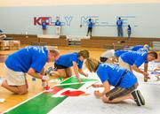 "Over 100 business officers from colleges and universities around the  country gathered at Kelly Miller Middle School in D.C. on July 28 to  help paint and revitalize the facility. The volunteer effort, supported  by TIAA-CREF and American University, was part of the National  Association of College and University Business Officers' annual meeting,  held that week in Washington.               As one team applies paint to a student-designed mural another group paints a new ""Kelly Miller"" sign in the gymnasium."