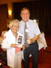 A total of 233 retirees on June 26 learned how to stay connected with their families, track personal finances and health care information and be entertained at the Riderwood Digital Tech Expo at Riderwood retirement community in Silver Spring. Joan Plapinger, the winner of door prize drawing for a Nook, posed with Bo Lunch, Riderwood's director of operations.