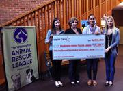 Mackenzie Keeley, Caps' Jeff Schultz's fiancée; Mandy Flemmer, Caps' Karl Alzner's fiancée; and Carmen Brouwer present Washington Animal Rescue League's Chief Operating Officer Mary Jarvis with a check for $31,320, which was raised through the sale of the 2012 Caps Canine Calendars.