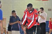 Washington Capitals right wing Joel Ward helps show a student at Ronald Brown Middle School how to hold a hockey stick.