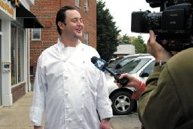 Michael Landrum of Ray's Hell Burger talks to the press after his Arlington restaurant fed President Barack Obama.