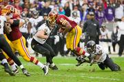 Redskins running back Alfred Morris tries to escape an ankle tackle by safety Bernard Pollard.