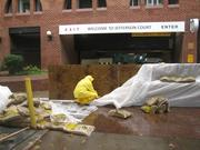 Workers stack sandbags to protect the garages at Jefferson Court on K Street NW.