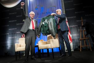 David Rubenstein, right, presents Warren Buffett with a Woodrow Wilson High letter jacket. Photo by Sam Kittner/The Economic Club of Washington, D.C.