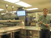 Clyde's President Tom Meyer, sushi knife in hand, tours the Hamilton kitchen.