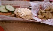 Chicken topped with goat cheese and fried pickles at Smashburger.