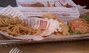 A Buffalo chicken sandwich and haystack onions at Smashburger.